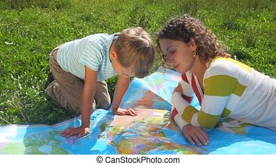 young woman and boy sitting on green grass, looks at political map