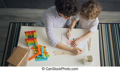 Young woman and child drawing together making picture with pencils in flat