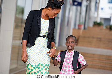 young woman and her child on the way to school.