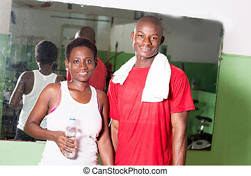 Young woman and her coach in a gym.