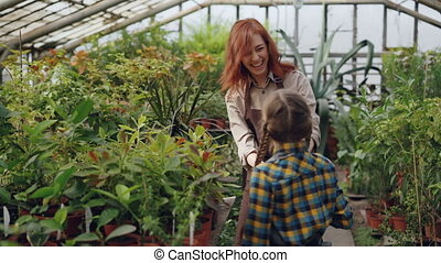 Young woman and her daughter are sprinkling water on flowers, child is having fun and spraying her mother with laughter. Growing plants and happy family concept.