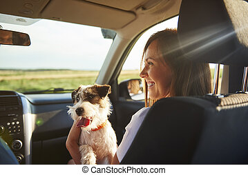 Young woman and her dog traveling together