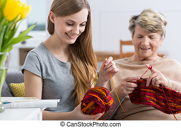 Young woman and her grandma knitting