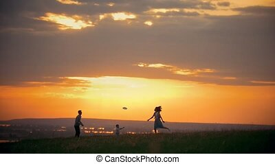 Young woman and her husband playing on the field, standing next to their little son, sunset summer evening - slow-motion