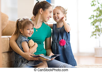 Young woman and her little children reading books at home