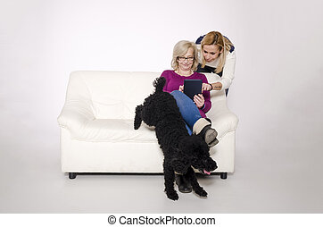Young woman and her mother sitting on the couch with a black poodle.