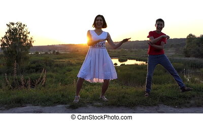 Young Woman And Her Son Dance Disco Happily on a Lake Bank at Sunset in Slo-Mo