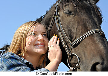 young woman and horse in sunny day
