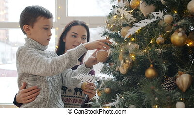 Young woman and little child son decorating New Year tree with beautiful decorations at home