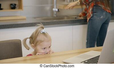 Young woman and little girl are in front of laptop in kitchen interior.