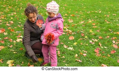 young woman and little girl gathering autumn maple leaves