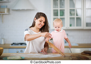 young woman and little girl in the kitchen play cooking