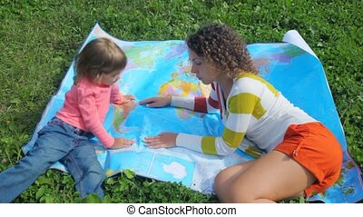 young woman and little girl lying on green grass, looks at...