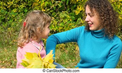 young woman and little girl playing with autumn leaves in park