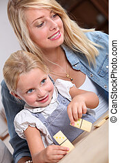 Young woman and little girl playing with dominoes