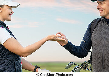 Young woman and man are playing golf
