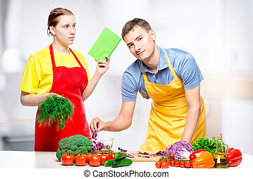 young woman and man cook together diet salad, shooting in the kitchen