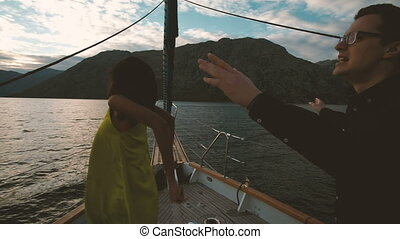 Young woman and man dancing on deck of ship in evening outdoors.