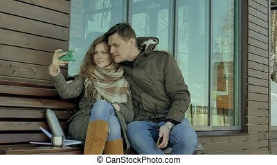 Young woman and man do selfie on the phone and drinking tea from a thermos bottle in a spring park sitting on a bench