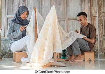 young woman and man drawing batik