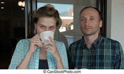 Young woman and man drinking tea standing on balcony indoors.