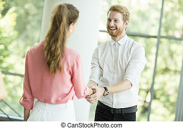 Young woman and man handshaking