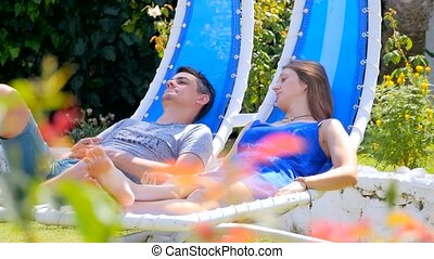 Young woman and man in rocking chairs