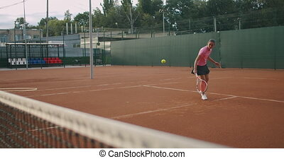 Young woman and man in sportswear playing tennis. Medium shot of female tennis player.
