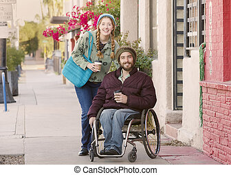 Young Woman and Man in Wheelchair with Coffee