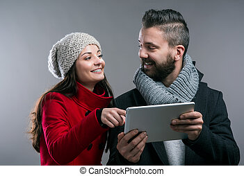 Young woman and man in winter coats with tablet