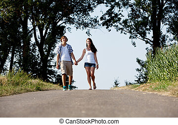 young woman and man is walking on a road in summer outdoor