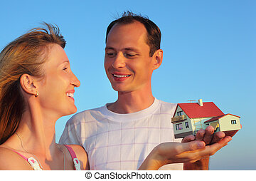 Young woman and man keeping in hands model of house with garage against sky in summer