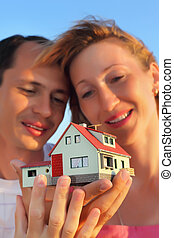 Young woman and man keeping in hands model of house with garage