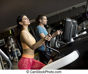 Young woman and man on elliptical stepper trainer exercising in gym