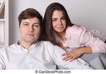 Young woman and man pose together on armchair in living room