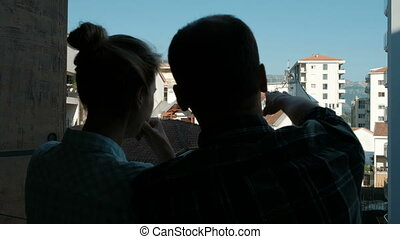 Young woman and man standing on balcony of apartment in summer.