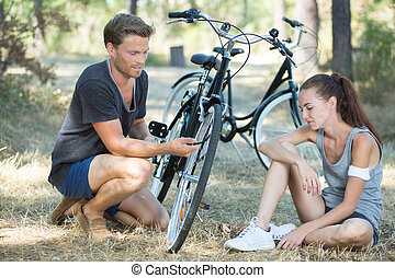 young woman and man with bicycle sitting in a park
