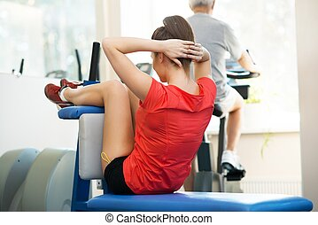 Young woman and senior man doing different fitness exercises