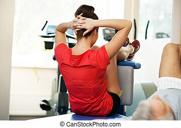 Young woman and senior man doing abdominal exercises in fitness club