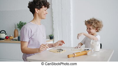 Young woman and small boy putting flour on dough then having...