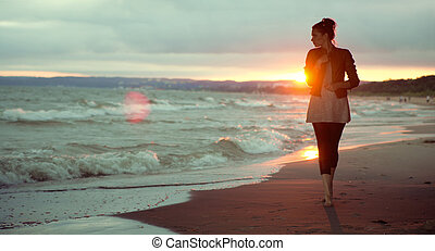 Young woman and the sunset in the background
