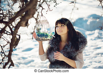 Young woman and winter birds in a cage