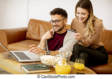 Young woman and young man using laptop for onlin payment while sitting by sofa at home