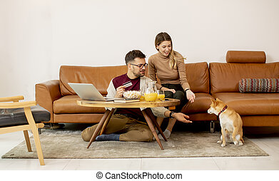 Young woman and young man using laptop for onlin payment while sitting by sofa with their shiba inu dog at home