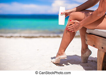 Young woman apply cream on her smooth tanned legs at...