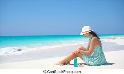 Young woman apply cream on her smooth tanned legs at tropical beach