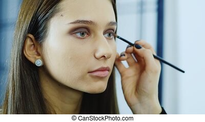 Young woman apply makeup around the eyes