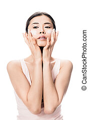 Young woman applying anti-aging moisturizer on her cheeks
