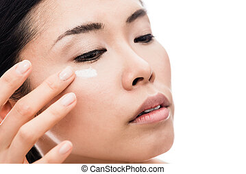 Young woman applying anti-wrinkles eye moisturizer -...