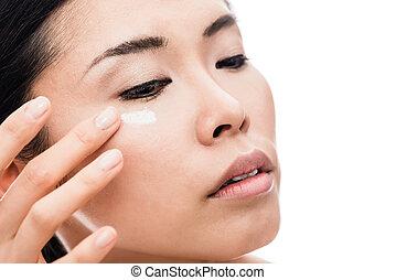 Young woman applying anti-wrinkles eye moisturizer -...